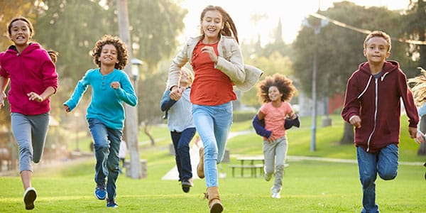 42311905 - group of young children running towards camera in park