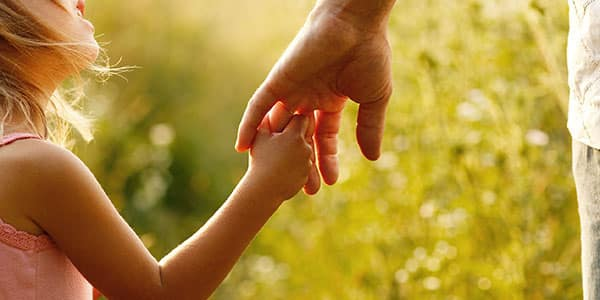 37407145 - a parent holds the hand of a small child